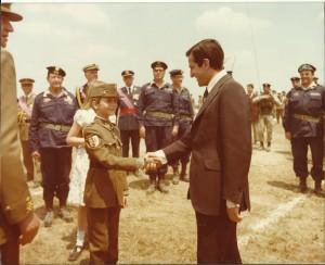"""El Príncipe de Asturias el día de su filiación saluda al Presidente del Gobierno, Don Adolfo Suárez(al fondo el Jefe del DAC """"Brunete"""", Gal. Milans del Bosch)."""