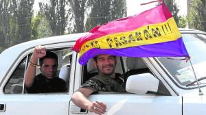 Angel and Rafa, who say they are from Spain, and volunteered to join pro-Russian separatists, ride a car in Donetsk