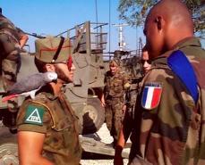"""Legionarios de la Compañia Austria en el destacamento Piper Camp conversan con un soldado francés en las afueras de Skopje dentro de la misión """"Cosecha Esencial"""" de la OTAN"""