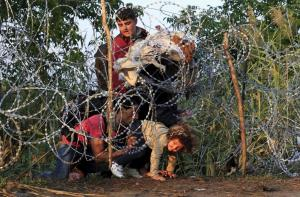 syrian-migrants-cross-under-a-fence-as-they-enter-hungary-at-the-border-with-serbia-near-roszke